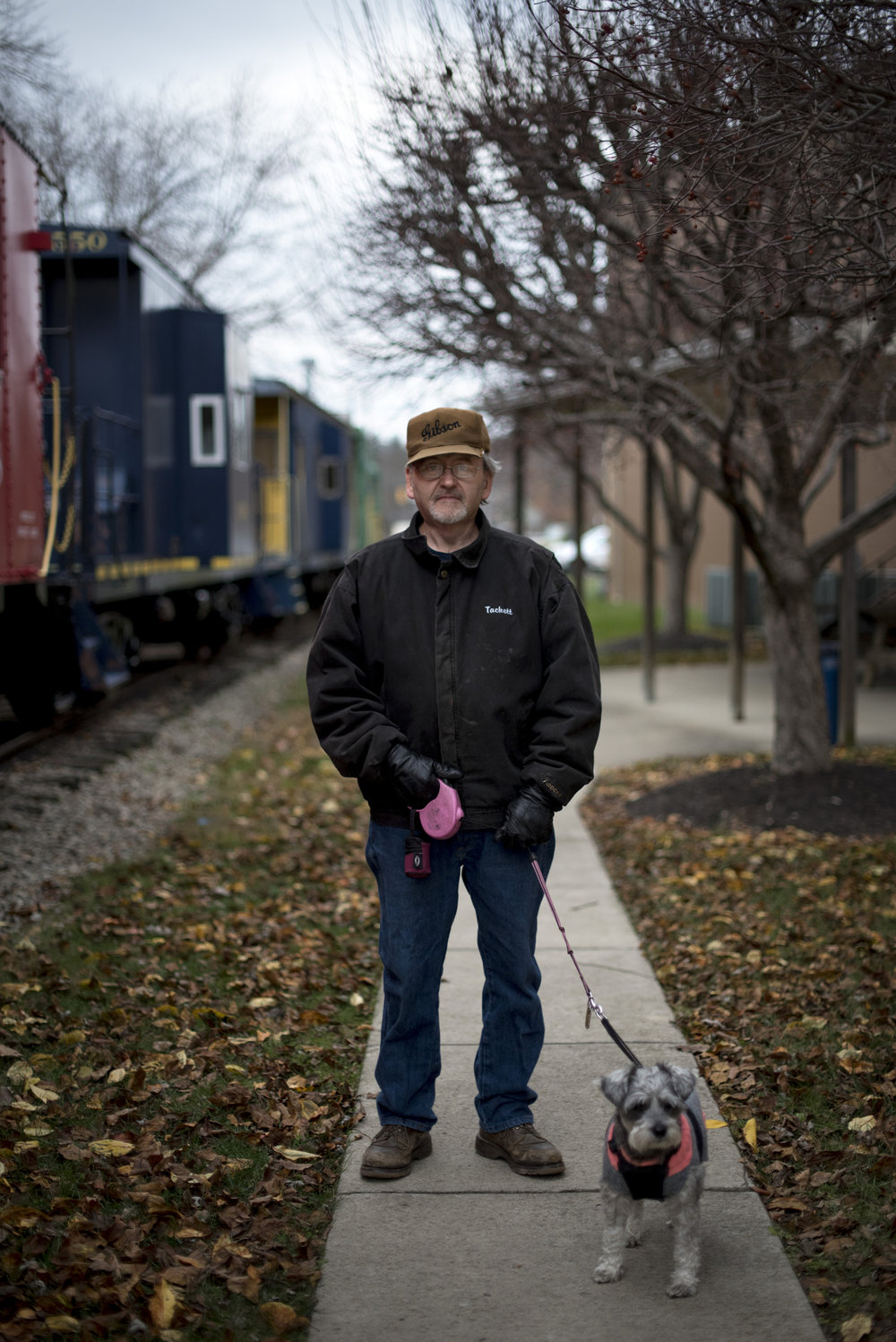 Mike Tackett walks his dog Maggie next to the Hocking Valley Scenic Railway in Nelsonville, Ohio on Dec. 9, 2016. Tackett is now retired, and used to work in the Nelsonville Weld Shop.