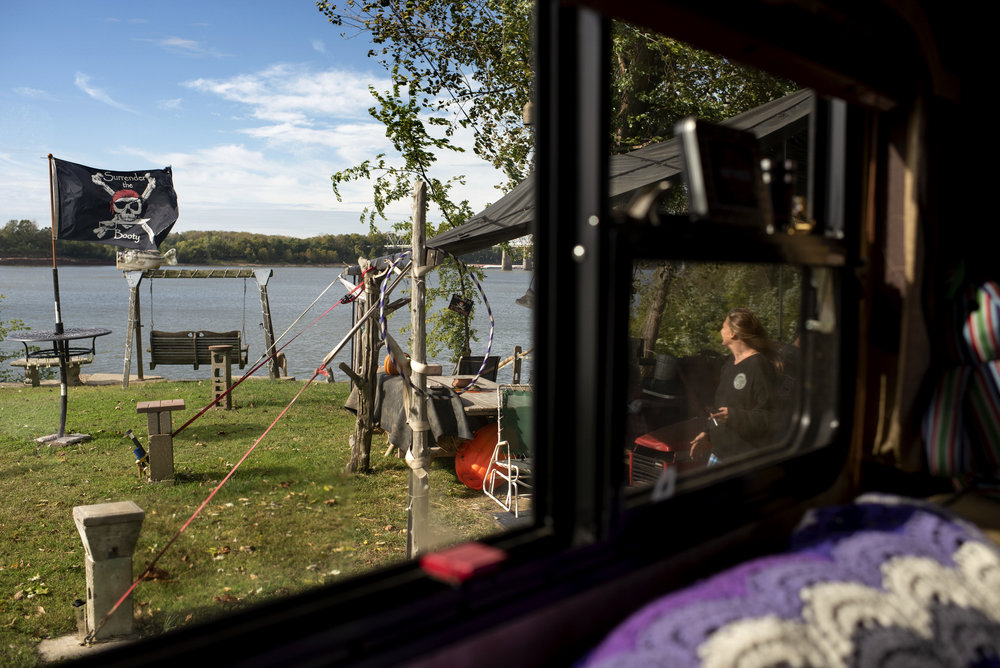 Val Hufford is one of many Evansville, Indiana-area people who spend their weekends – and sometimes their whole lives – living in campers or trailers on stilts along the Ohio River. Val enjoys a morning cigarette as she walks to sit in her bench overlooking the river on Oct. 21, 2017.