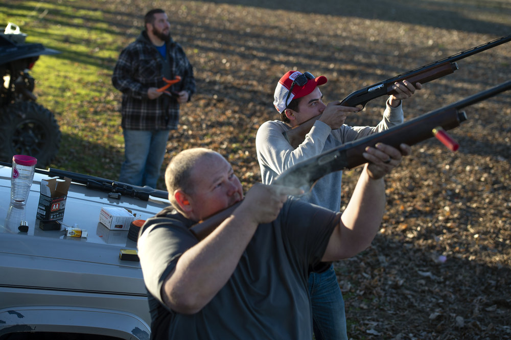 Evan Gaultney, right, and Kevin Holder shoot at a clay target with friends in an empty field behind the riverbank in Dade, Ky. on Nov. 28, 2017. Evan's friend Derek DeTalente, not pictured, grew up coming to the river because both sets of his grandparents had lots at the riverbank. DeTalente said when he was younger, there used to be more people and other kids around. He remembers riding bikes around trails under the bridge.