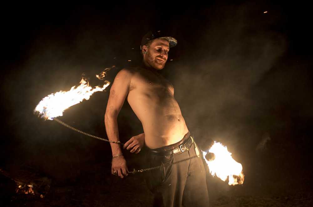 Nick Will puts on a show of spinning fireballs for a crowd of friends and people he just met at the riverbank in Dade, Ky. on October 21, 2017. That evening was Will's first trip to the river community. Though he came to visit friends, he ended up visiting other camps to perform his fire show multiple times.