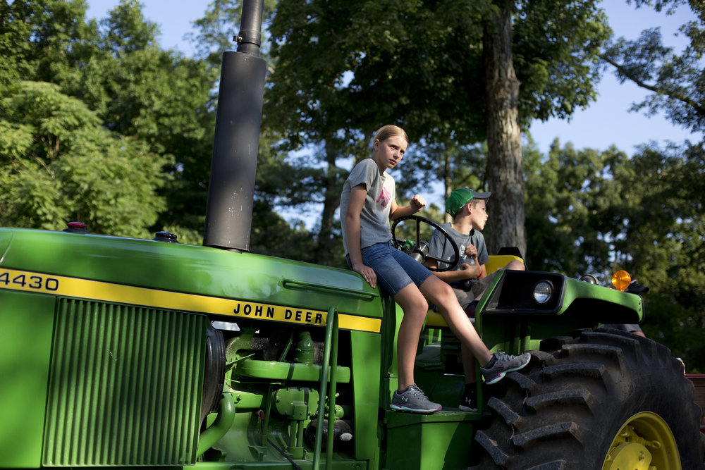 Shayla Sander, 12, and her cousin Trace Buechler, 11, both of Celestine, sat on Trace's fathers tractor, Kris Buechler, before the hay ride on June 23, 2018 as part of Celestine, Indiana's 175th anniversary celebrations.