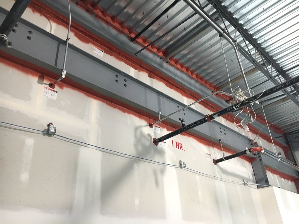 Fire Stopping - The application of fire rated caulk material applied where a mechanical or electrical penetration was required through a wall or ceiling structure.