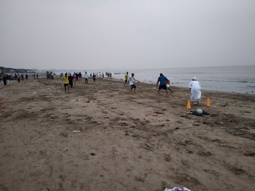 Game taking place on Versova Beach as the sun sets.