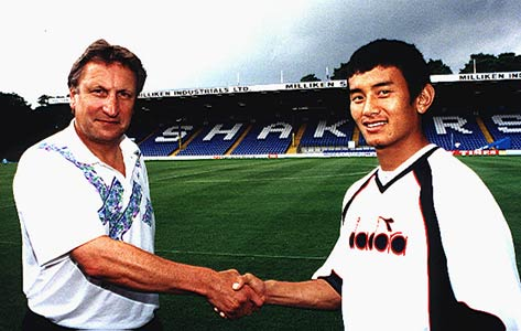 Bhutia making history in 1999 as he signs for Bury, shaking hands with the timeless figure of Neil Warnock (Cardiff City's current manager)