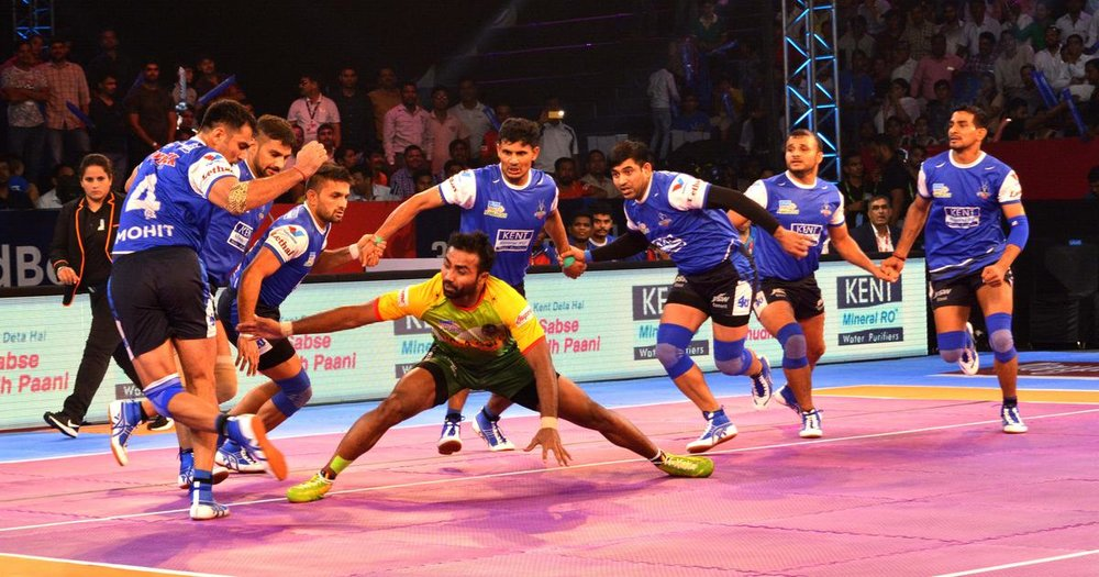Kabaddi in action... Attempted explanation: the player in yellow is attempting to tag one of the blues, and would then attempt to dash back into his own half without being caught to achieve a point… I think.