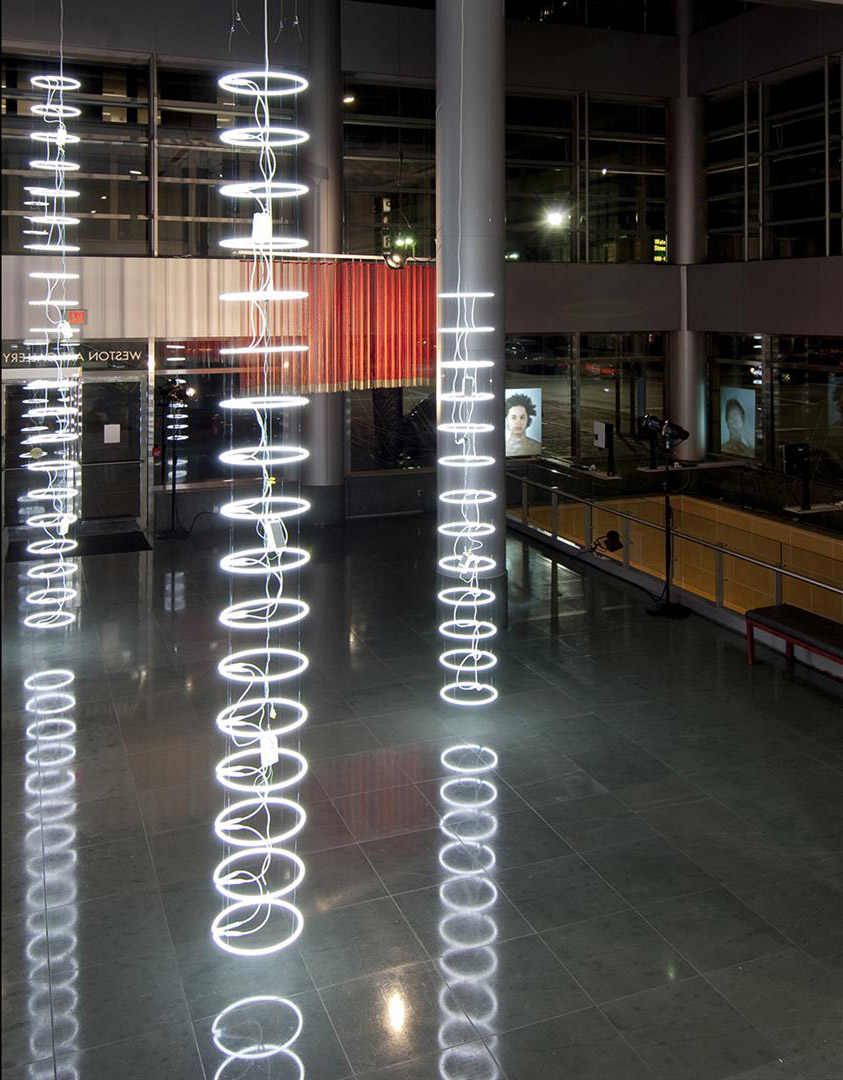 """Spiracles   Neon, transformers, monofilament  #1) 18' 2"""" x 17½"""" diameter (21 rings)  #2) 16' x 17½"""" diameter (17 rings)  #3) 12' x 17½"""" diameter (13 rings)  2012"""