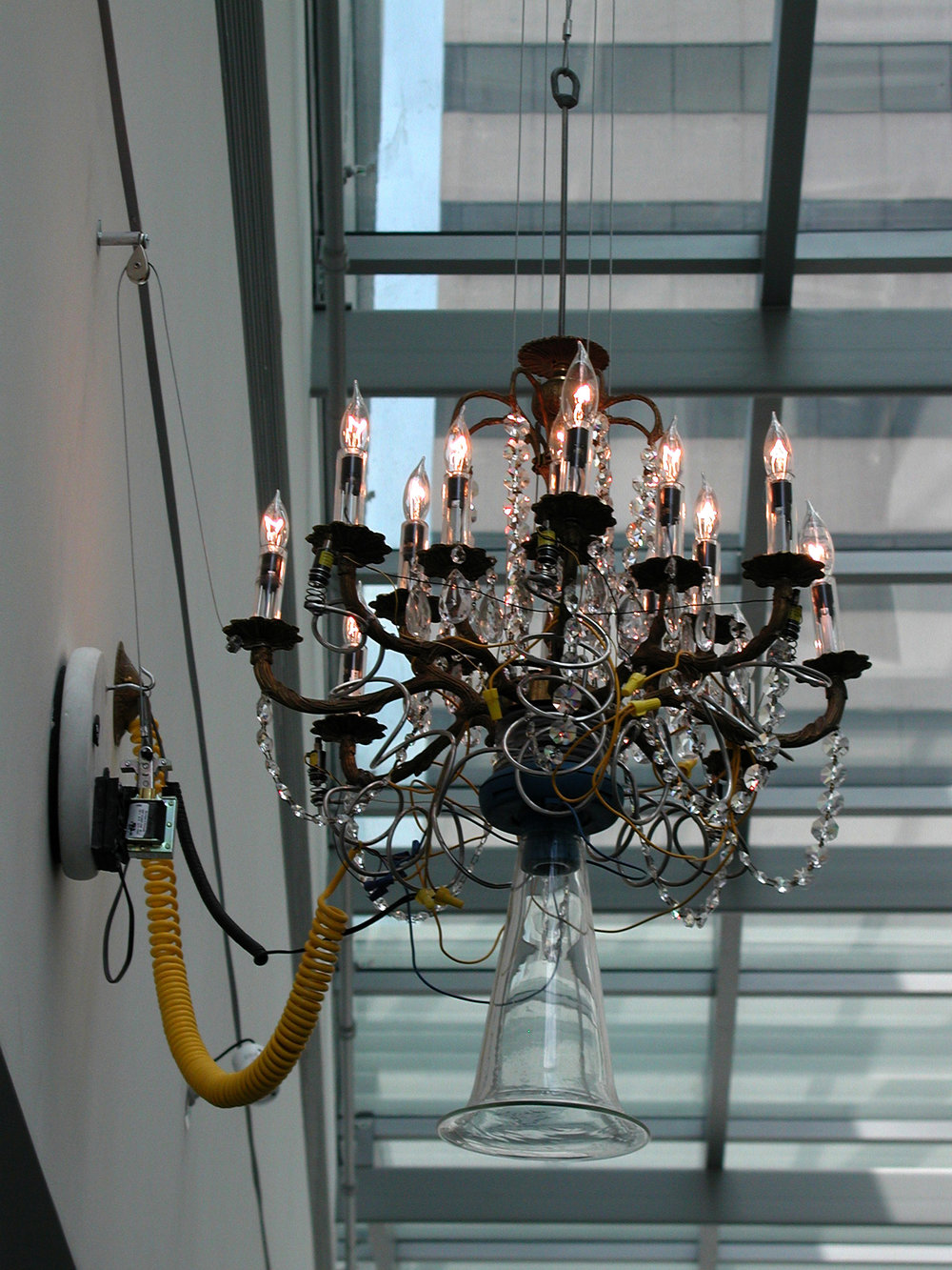 Singin' & Ringin' Chandelier   modified antique chandelier, hand-blown glass speaker bell, digital soundboard, electronics, solenoids, cable,  pushbutton, original recordings by soprano Blythe Walker  approximately 3' diameter x 3.5' high / 2002-3