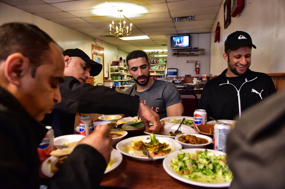 From left, Mohammed Almarhoon, his brother Hussain, Hidar, Hussain, and Ali (not pictured), all family from Saudi Arabia, dine at the Jerusalem Halal Market.  The types of food available are an okra stew called Bamieh, Goat Briyani, seasoned potatoes and lavish bread, as well as many other Middle Eastern dishes.