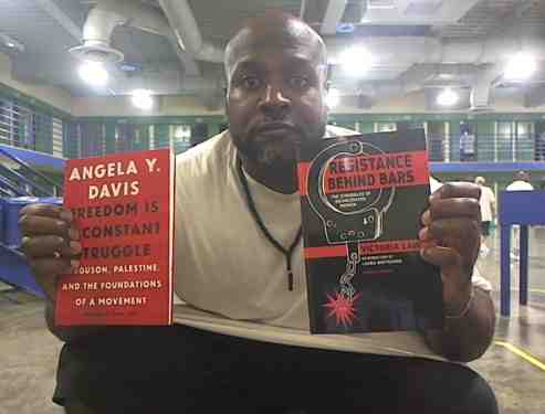 Khalfani with books by Angela Davis and Victoria Law