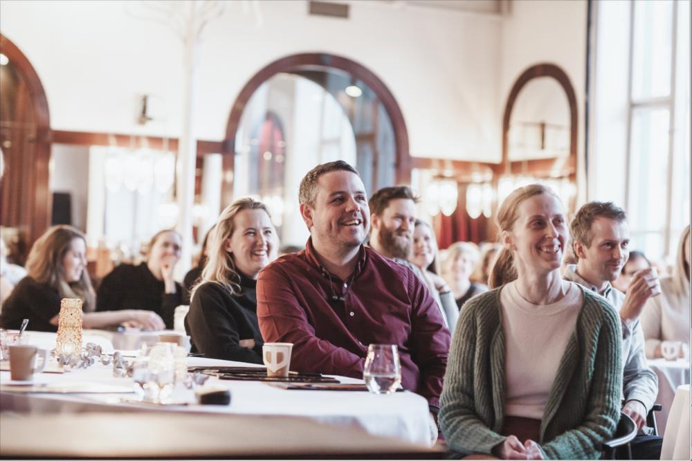 En haug smilende folk med fokus på Morten Wikstrøm som blant annet sitter i styret til CreativeMornings.