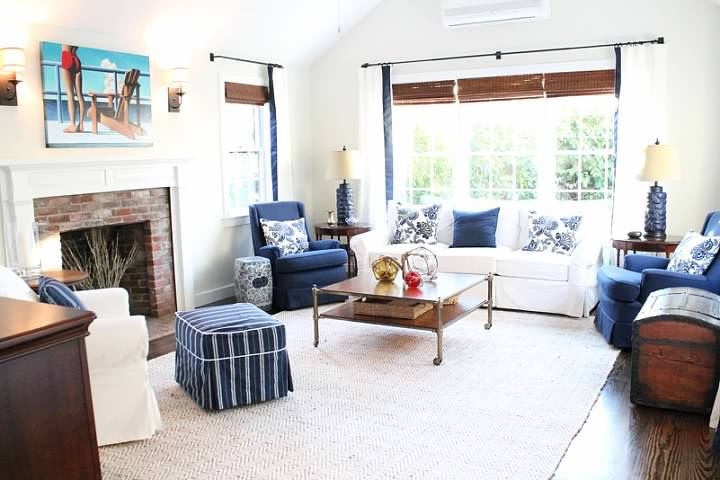 Above, a brass and maple Barclay Butera coffee table is adorned with Homegoods accents and Ikea's budget ottomans compliment custom upholstered navy chairs.