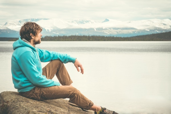 man_reflecting_by_lake_with_mountains.jpg