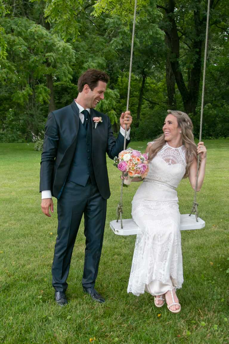 Bride and groom have a playful moment on swing