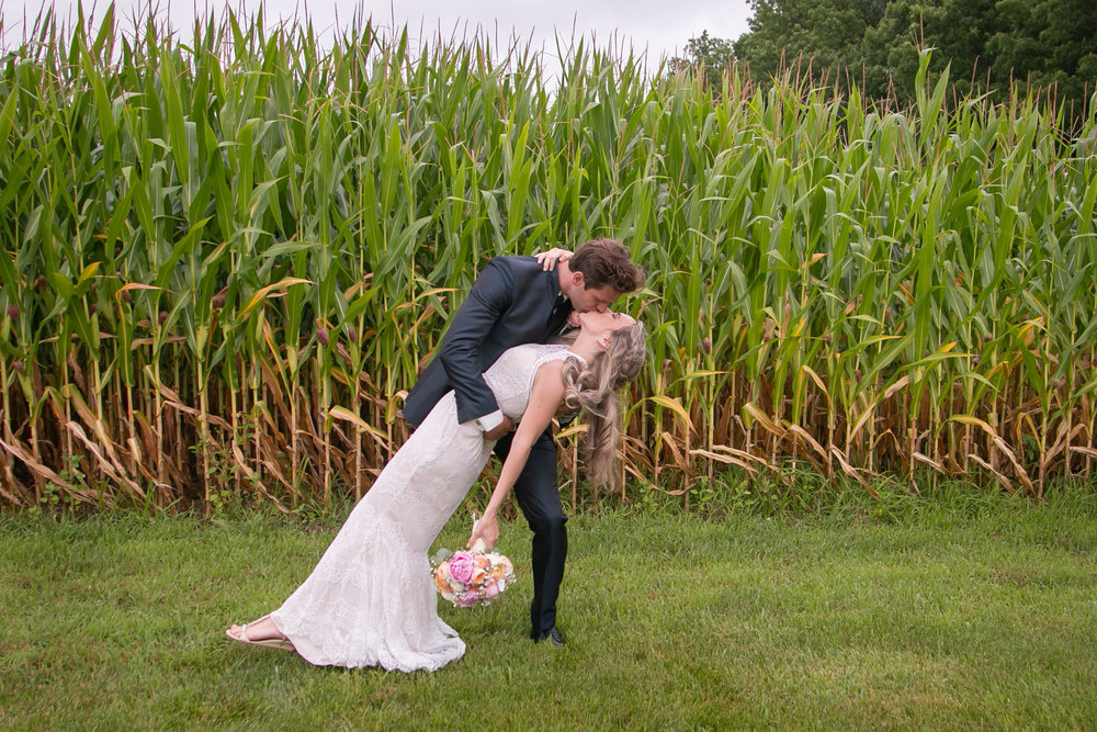 Bride and Groom Kiss in Front of Cornfield at Barn Wedding Venue
