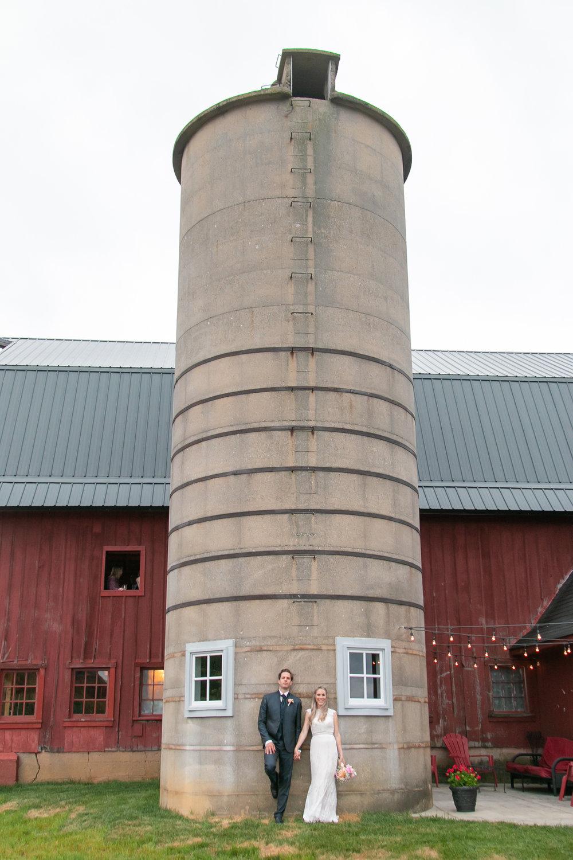 Bride and Groom Pose by Silo at Barn Wedding Venue