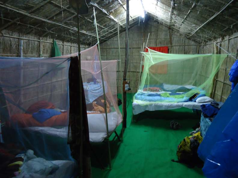 Inside our straw castles. Four to a hut! Mosquito nets strung between bamboo poles; industrial green carpet (over straw over mud) keeps out the worst of the damp.