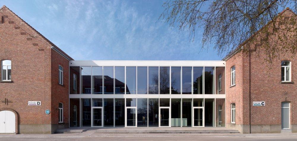Gevel van de vernieuwde POV-campus, waarbij twee gerenoveerde gebouwen aan elkaar gekoppeld werden door middel van een constructie met glazen facade.