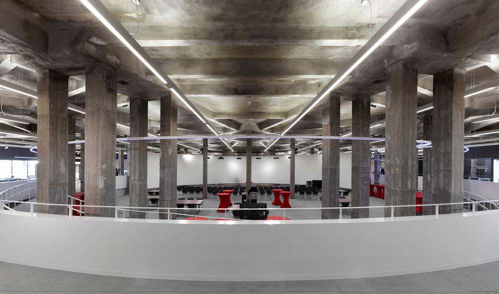 Panoramabeeld van de voorstellingsruimte. Beeldmateriaal wordt tijdens exposities weergegeven op het grote doorlopend witte doek.