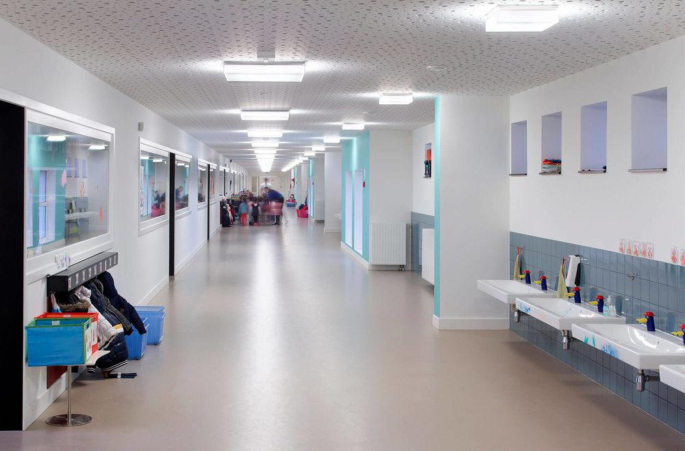 Lange gangen, voorzien van een akoestisch plafond, verbinden de verschillende klaslokalen met elkaar.