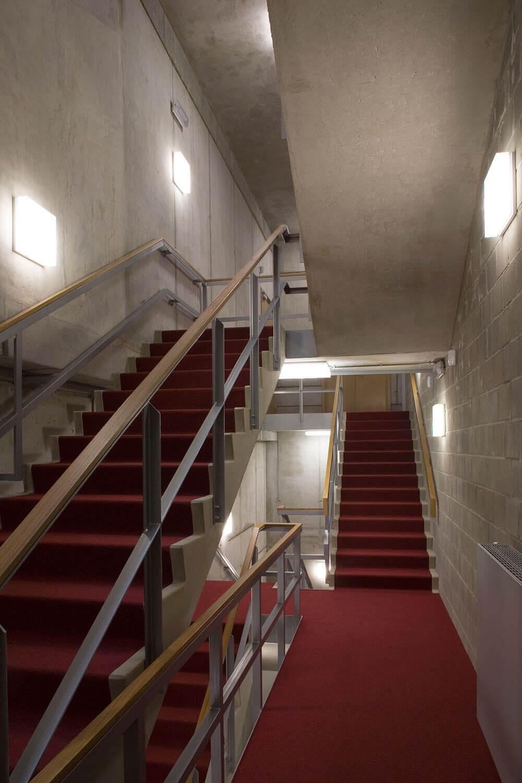 De trappenhal werd grotendeels uit beton vervaardigd, maar bekomt door de open structuur en het tapijt toch een ruimtelijk gevoel.