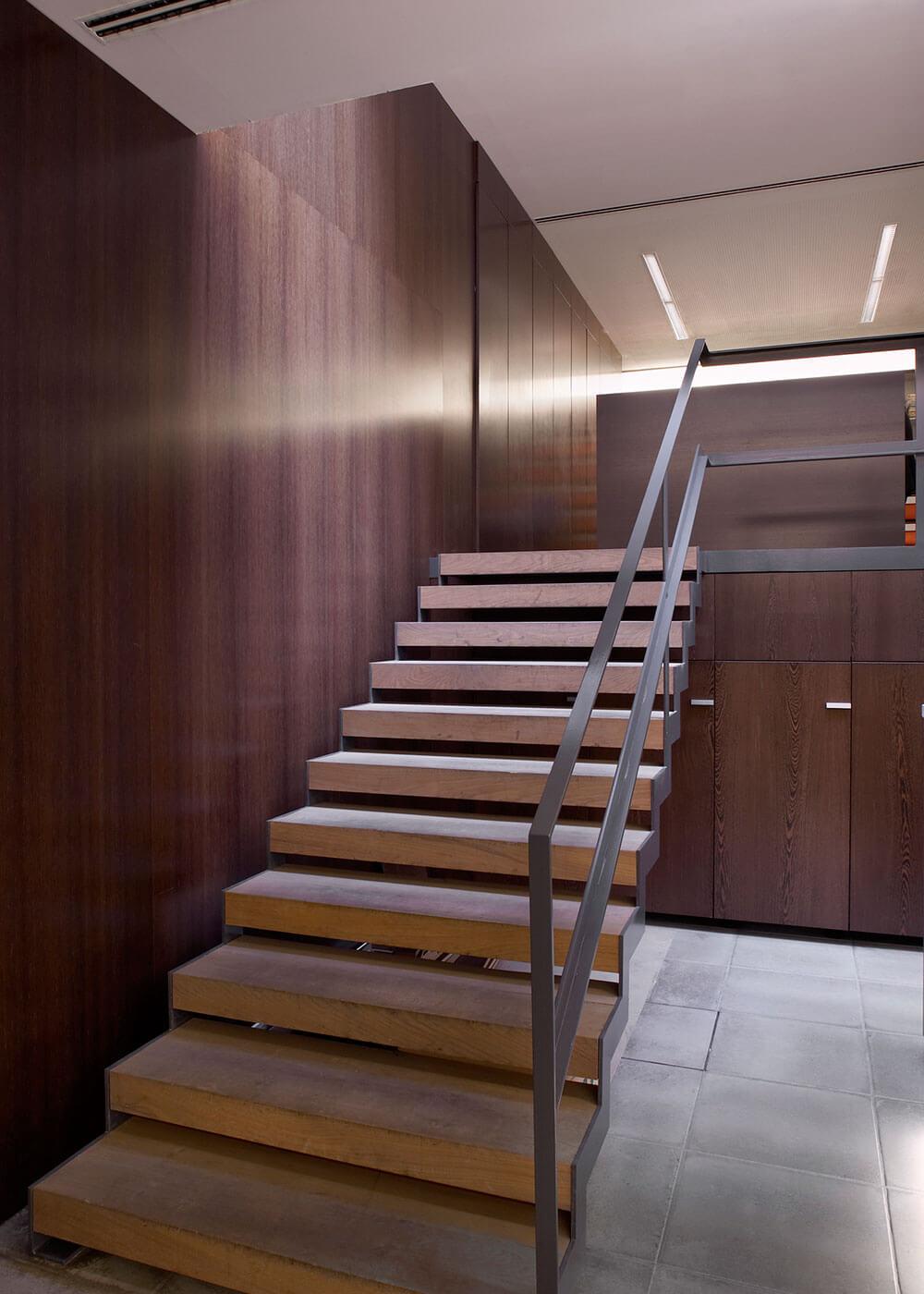 De trap sluit aan bij het omliggend interieurdesign en leidt naar de directiekantoren en het secretariaat.
