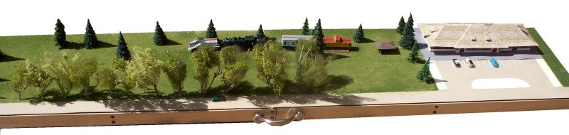 This is a scale model of the Depot and Railroad Heritage Park. The Union Pacific mainline is to the top of the model, while First Street is along the bottom edge. The train consists of (from left to right) the snow plow, engine, bunk car, caboose. Unmodeled portions of the scene are whited out.