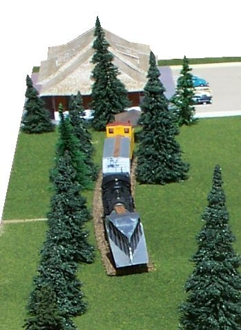 A closeup of the model of our 1950s snow train. From bottom to top: Snow plow, engine, bunk car, caboose. The train is on a slight curve facing south (eastbound).