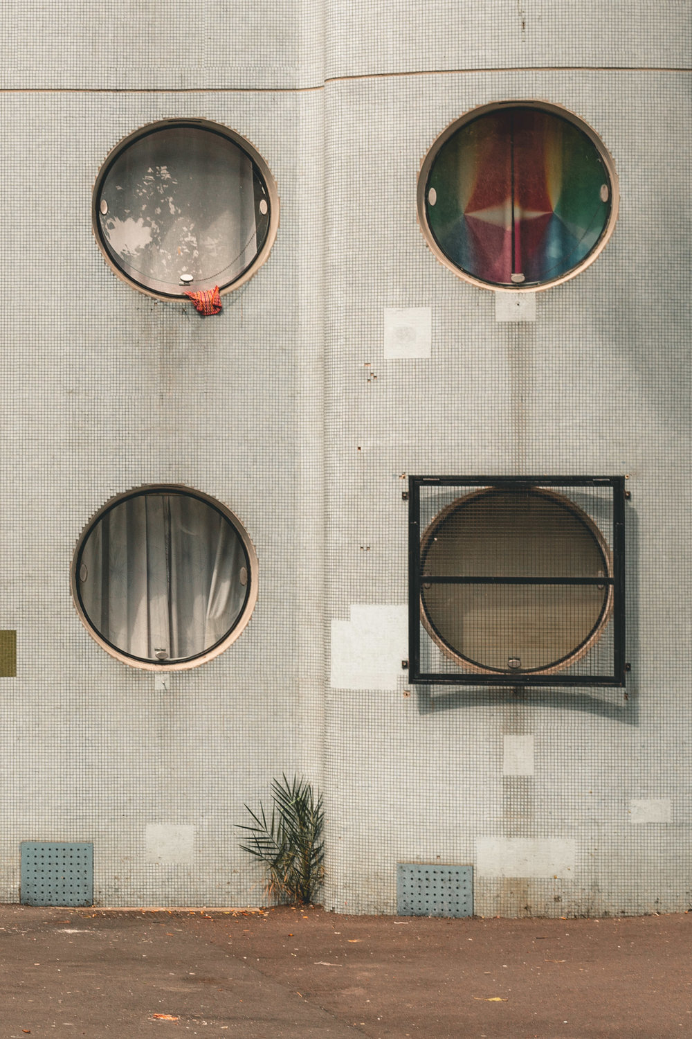 Architecture photograph detail series of the Tours Aillaud, Nanterre. Circular openings, with mosaic tile frontage. By Daniel Walker Photography