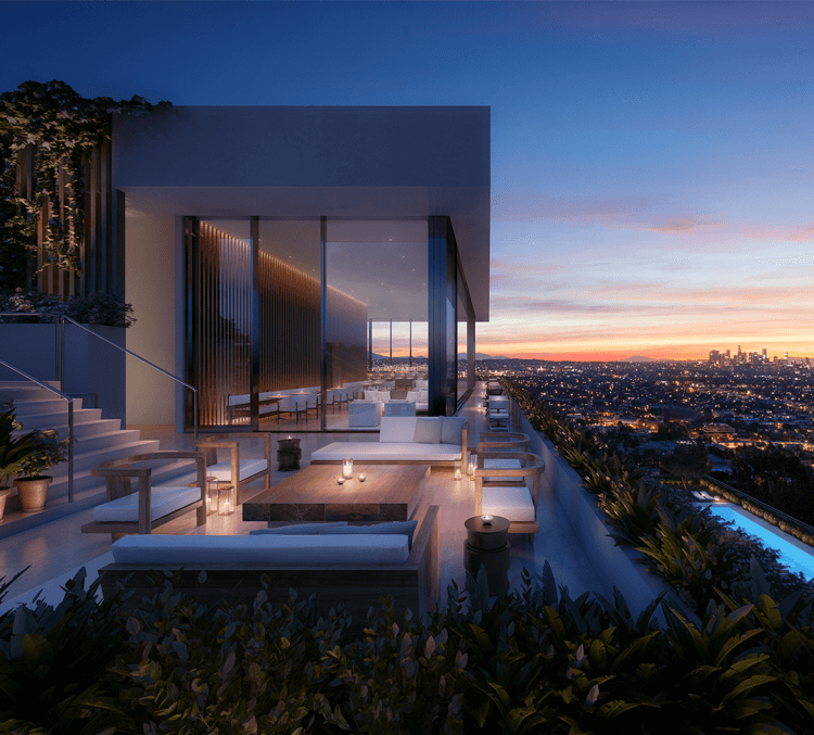Exterior view of an outside lounge area at the West Hollywood Edition at dusk with sweeping views of Los Angeles in the background.