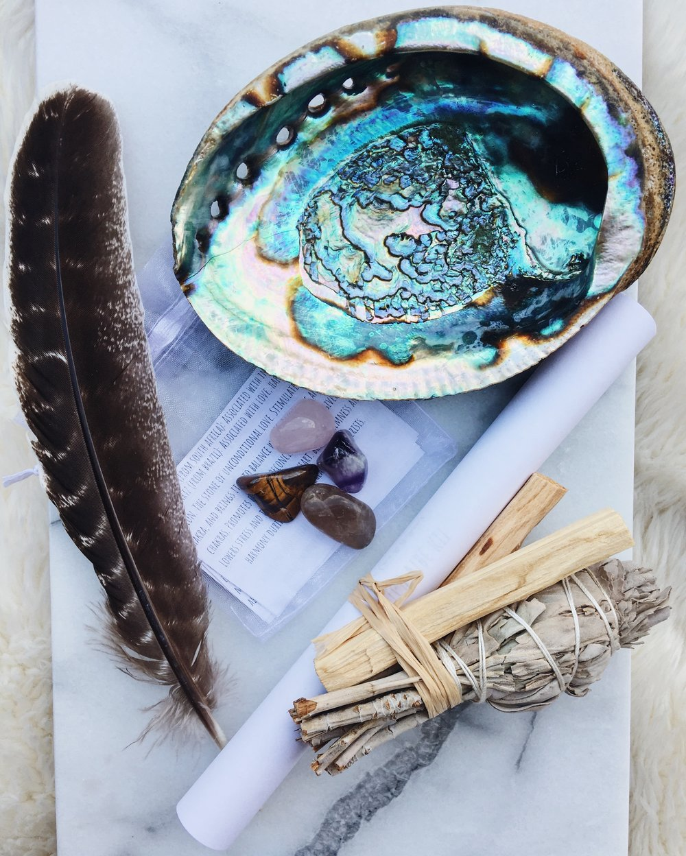 """big kit - This beautiful kit contains white sage, palo santo, crystals, a 5-6"""" abalone shell, and a barred smudging turkey feather. All of the contents were activated and cleansed by at least 2 soundbaths using crystal bowls & smudged with sage.$35/kit"""
