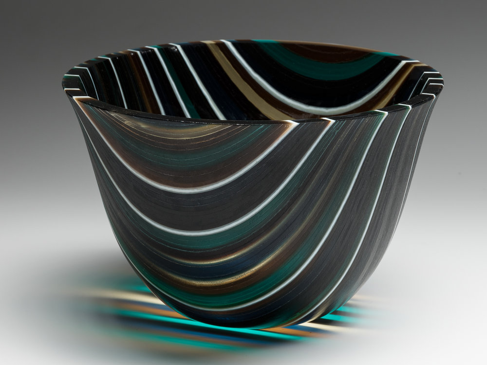 """Forest Like""    7""H X 9.5"" W   This vessel began with many 1/4"" strips of glass placed on edge and fused together to form one flat piece. A 16"" circle was then cut.  The ""slumping"" process is where the glass is placed on a mold and warmed in the kiln until the glass takes the shape of the mold. To gain this shape is a 3 step processes using graduated sized molds to attain the shape.  The edge is ground and polished using a grinding wheel and water."