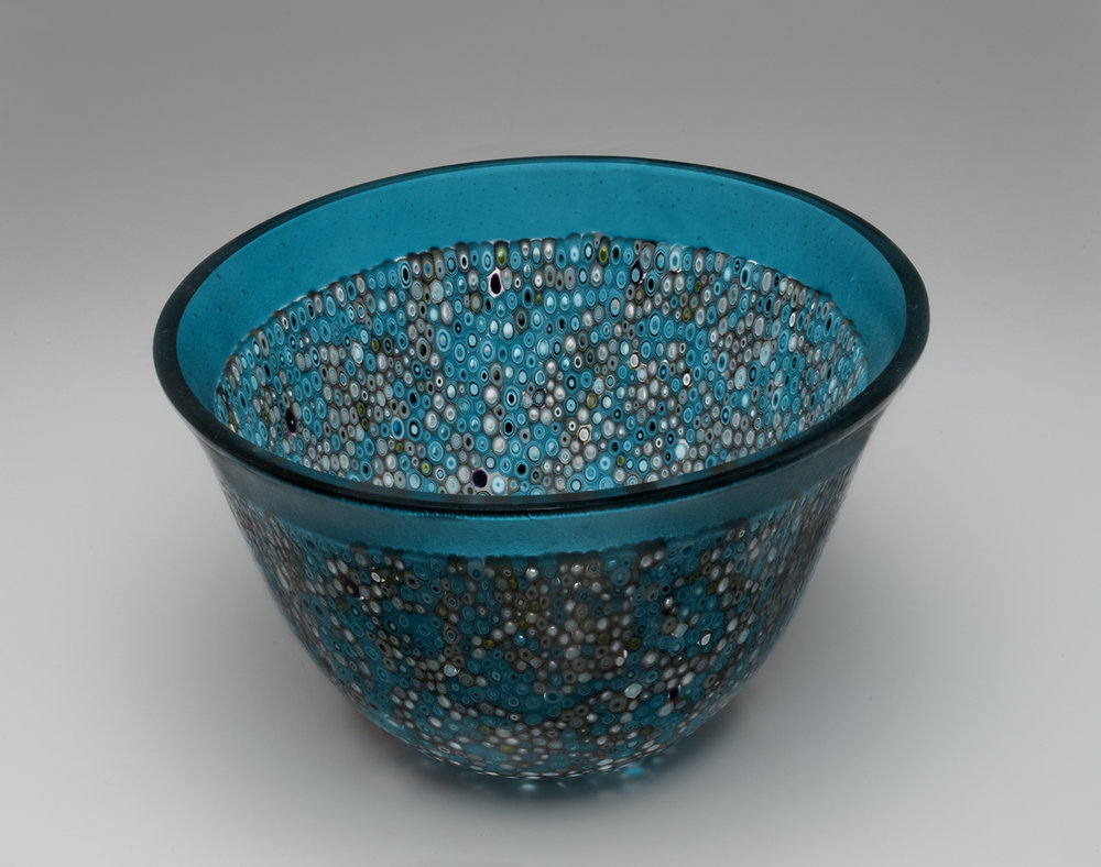 """Blue Bubbles""    7""H X 9.5"" W   This vessel began with many cutting a 16"" circle, then a 2"" outer ring was cut and pre-made murrine were placed within the ring. All of the components were fired to create a 16"" flat circle.  The ""slumping"" process is where the glass is placed on a mold and warmed in the kiln until the glass takes the shape of the mold. To gain this shape is a 3 step processes using graduated sized molds to attain the shape.  The edge is ground and polished using a grinding wheel and water."