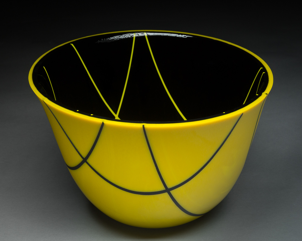 """Holy Yellow""    7""H X 9.5"" W   This vessel was created by cutting a 16"" disc of yellow and a 16"" disc of black. Thin strips of glass called stringers were laid on one side and the pieces were fired. Then the piece was turned over and stringers were added to the other side and it was fired again.  The ""slumping"" process is where the glass is placed on a mold and warmed in the kiln until the glass takes the shape of the mold. To gain this shape is a 3 step processes using graduated sized molds to attain the shape.  The edge is ground and polished using a grinding wheel and water."