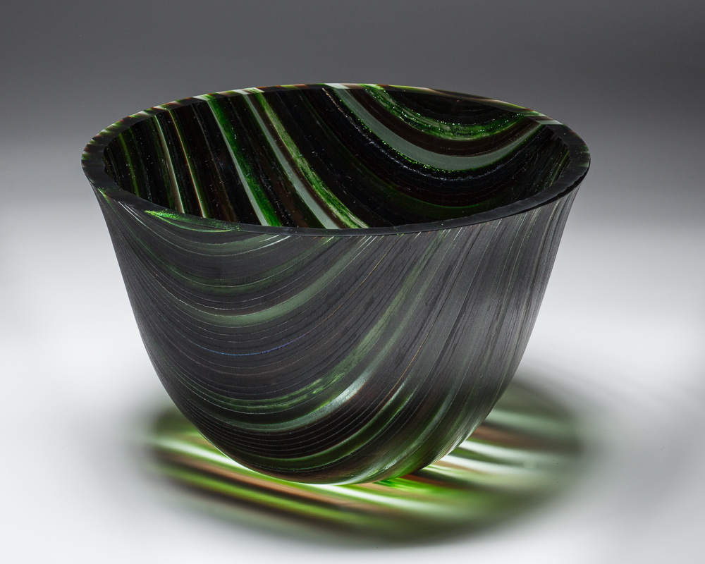 """Green Adventure""    7""H X 9.5"" W   This vessel began with many 1/4"" strips of glass placed on edge and fused together to form one flat piece. A 16"" circle was then cut.  The ""slumping"" process is where the glass is placed on a mold and warmed in the kiln until the glass takes the shape of the mold. To gain this shape is a 3 step processes using graduated sized molds to attain the shape.  The edge is ground and polished using a grinding wheel and water."