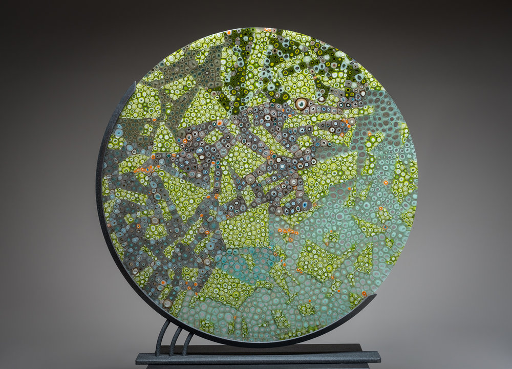 "Changing World  18"" sculpture in stand  This piece was created using pre-made glass cane which makes colored patterns that are revealed when the cane is cut into thin cross sections. The pieces of murrine are placed close together and fused in a kiln creating one solid piece."