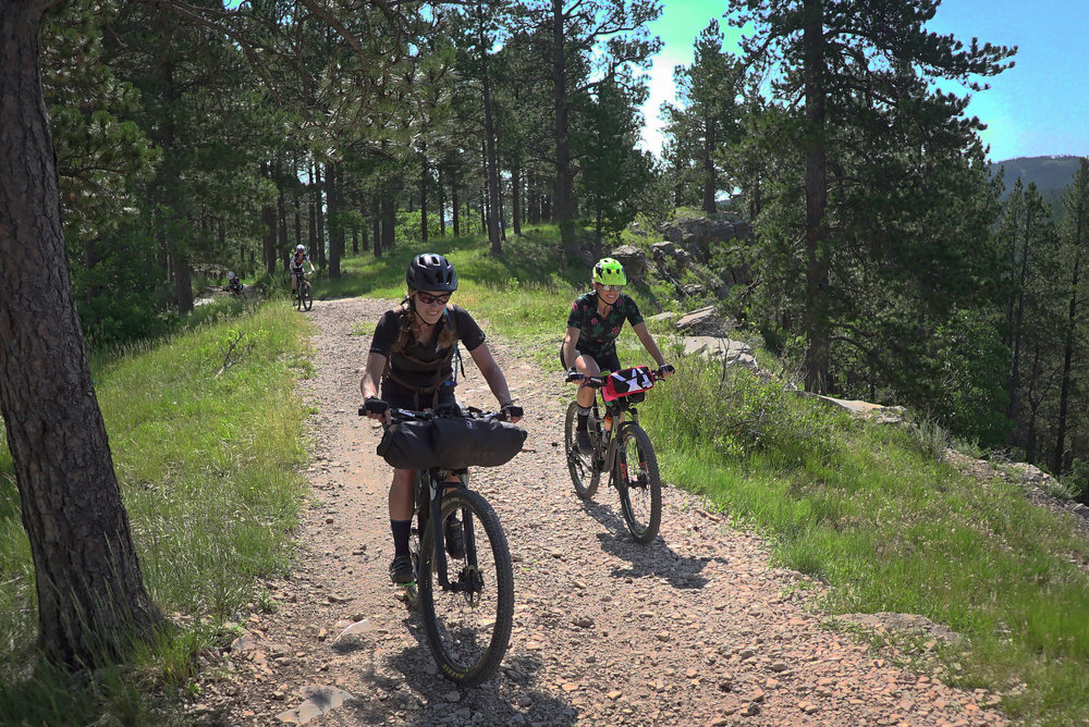 Kristi Jewett (left) and Diana Reth (right) smile as they reach the plateau following the steep fire road climb out of Sturgis, South Dakota.