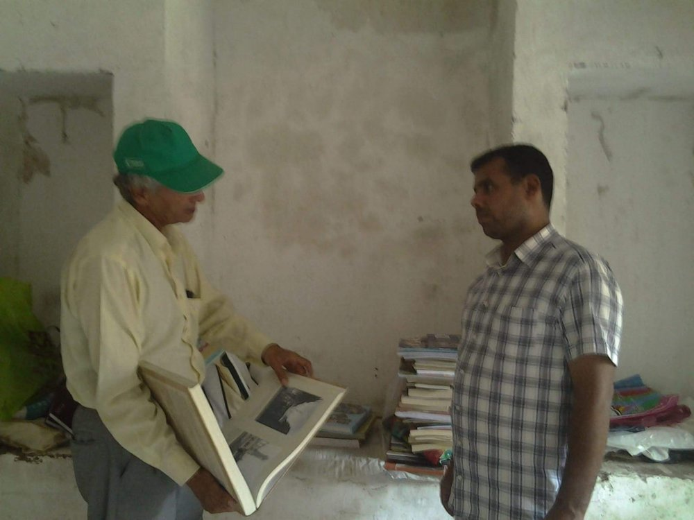 Mr. Al Taha shows his collected old books in the house to Mr. Akbaba.