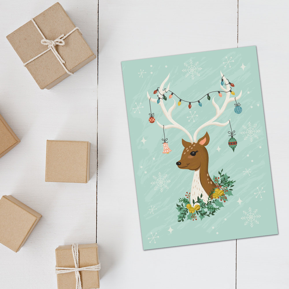 Christmas deer covered in holiday decor from twinkling lights to ornaments with a wreath, bells, and holly - the perfect greeting card for Christmas