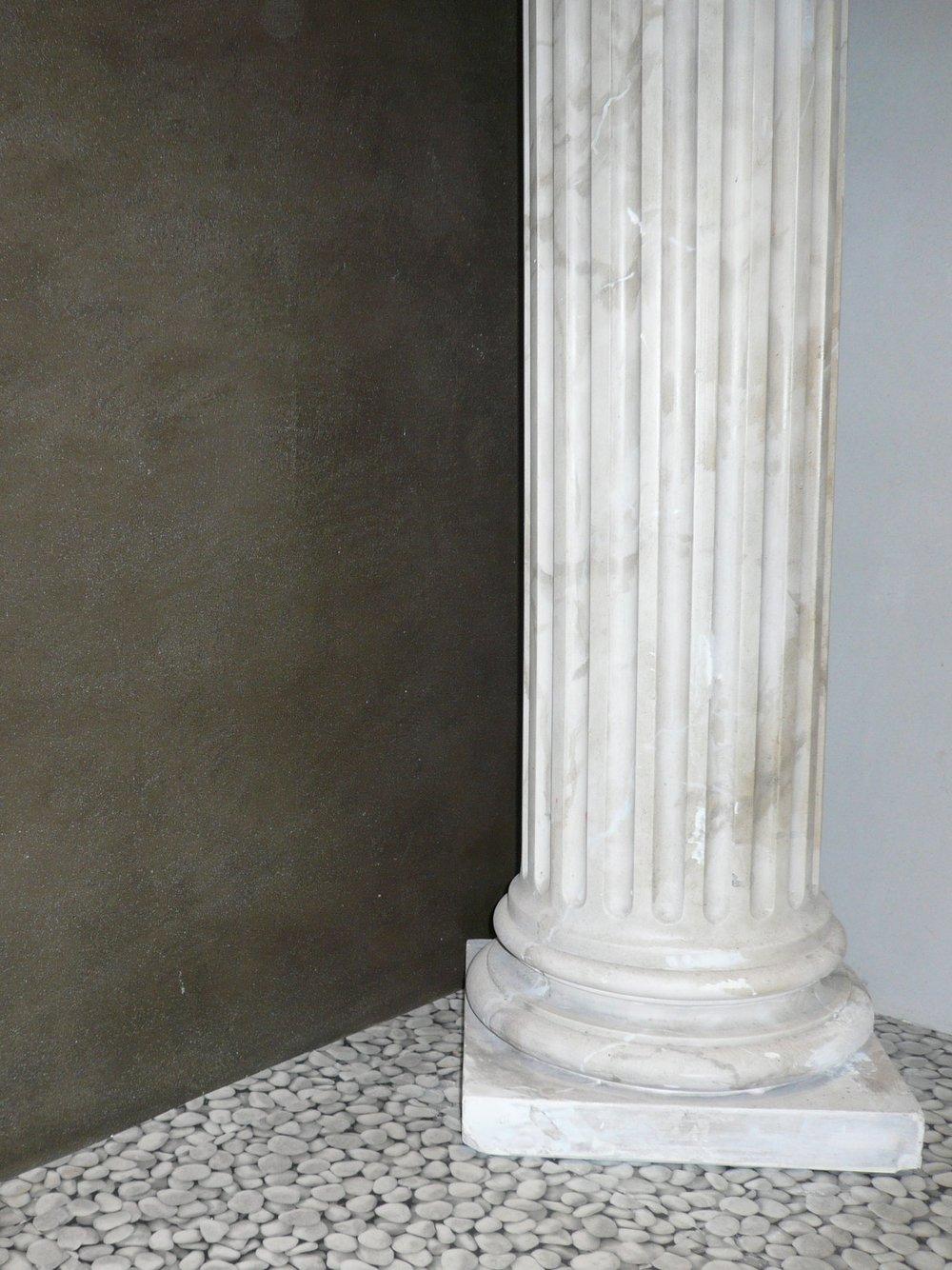 Marmorierte Säule vor Kalkwand