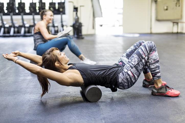 Woman Foam Rolling in Gym