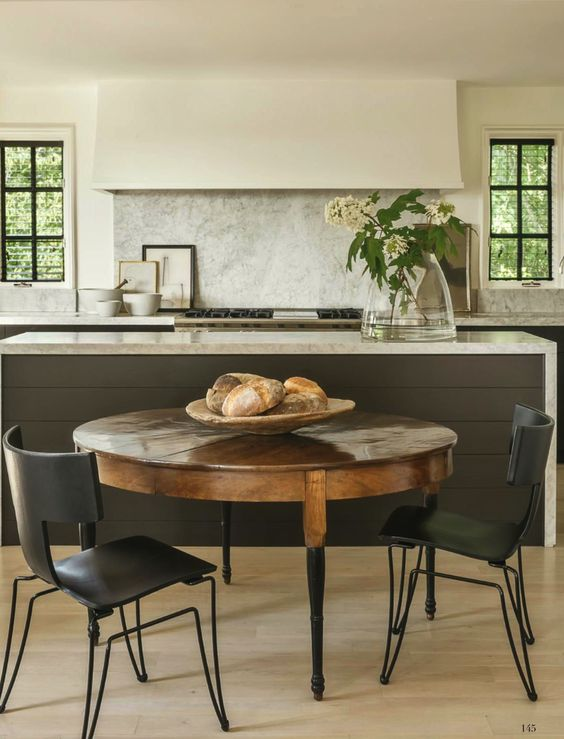 We are in love this sleek and warm kitchen designed by Betsy Brown. The clean lines of the hood and marble waterfall on the kitchen island form a simple and minimalist aesthetic, which is paired with the warmth of a more traditional and rustic wood table. Source: La Dolce Vita Blog