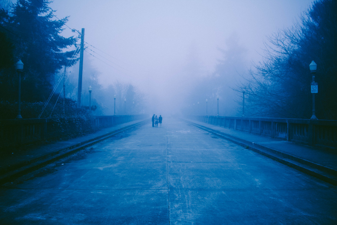 photo of a foggy bridge with three people off in the distance, partly obscured by the fog