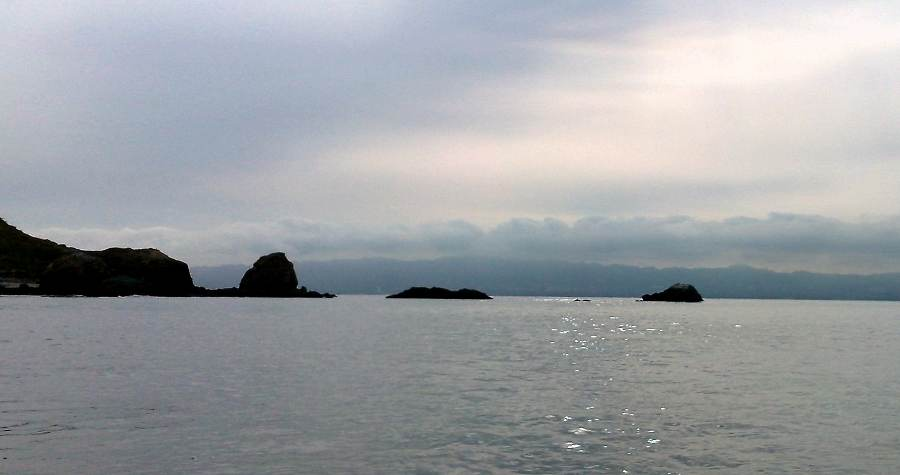 approach from the west - Approaching from the west but further out from the shore, one is tempted to hurry straight through the apparent gap, but the shoal isright in your wayfrom this angle. Instead, aim to the left toward the large haystack shaped rock, get in closer, and then turn to pass through on the angle shown above.