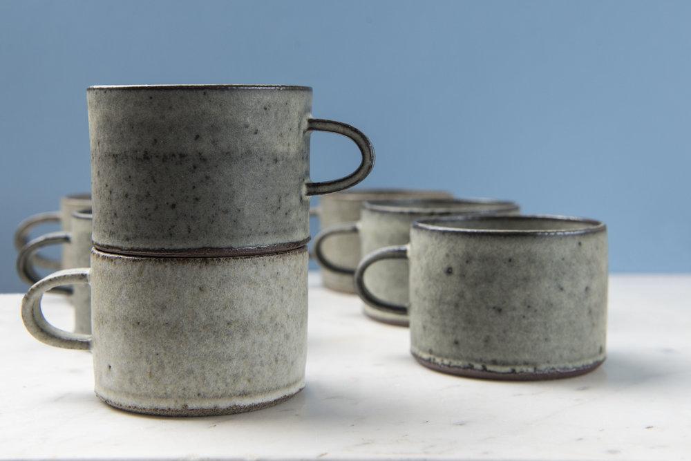 Hånddrejede kaffekopper i rød eller grå stentøjsler