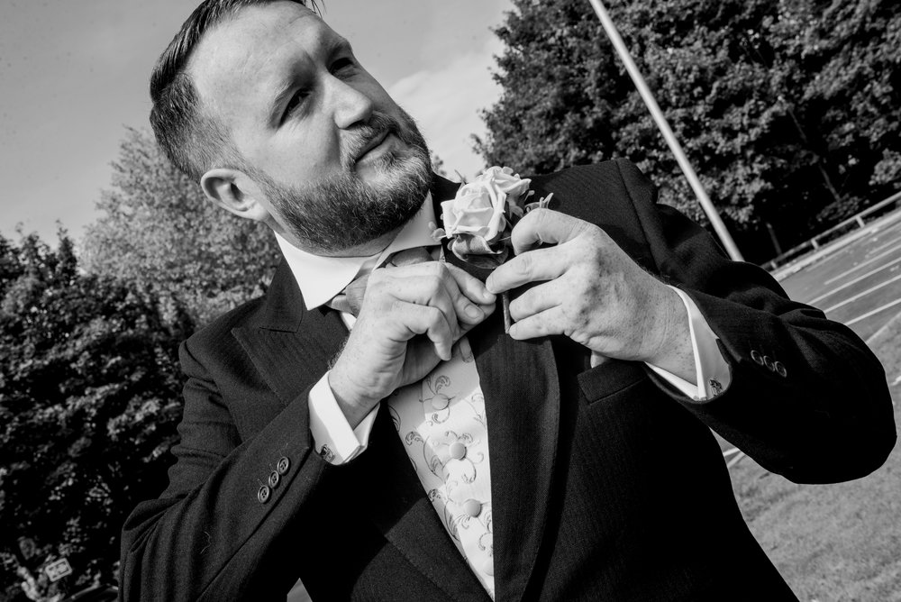 Black and white wedding photography groom adding his flower