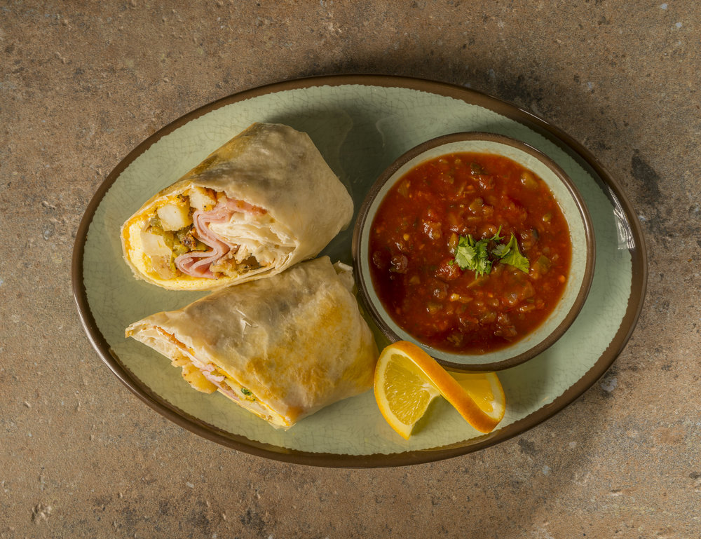 Breakfast Burrito - Eggs, choice of meat (bacon, sausage, ham), breakfast potatoes, green chilies, cheddar cheese, cilantro, sour cream on a flour tortilla with a side of salsa.$9.39