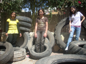 Hadil, Dalia, and the translator, Abeer pose with rubber tires being used to construct a jungle gym!