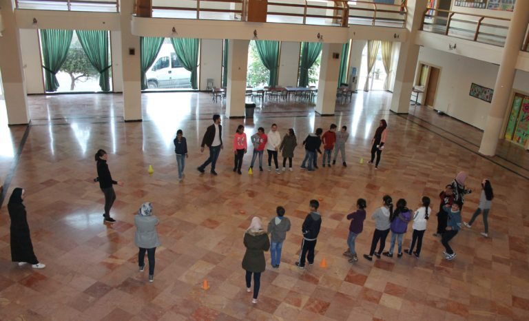 Academic students line up to play a racing game to practice English letters and numbers.