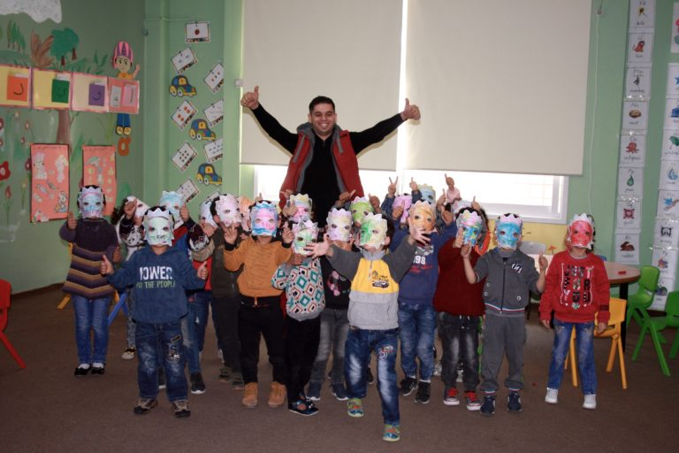 Core teacher Mahmoud and his students roar with their lion masks.