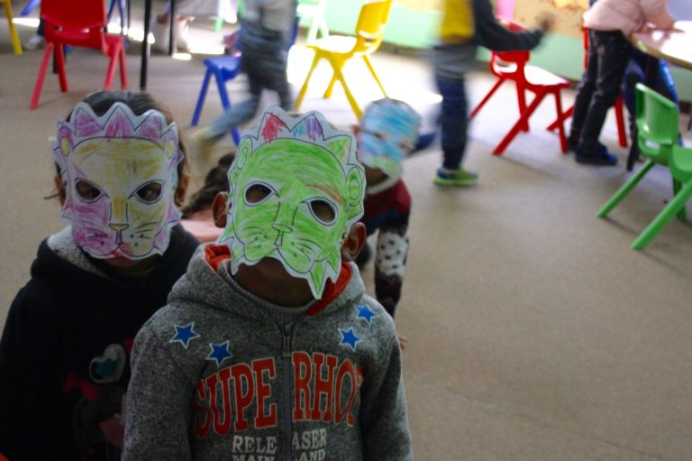 Two Core Early Childhood students pose in their lion masks.
